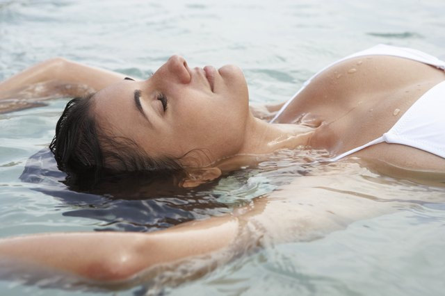 Young woman floating in sea, eyes closed, close-up