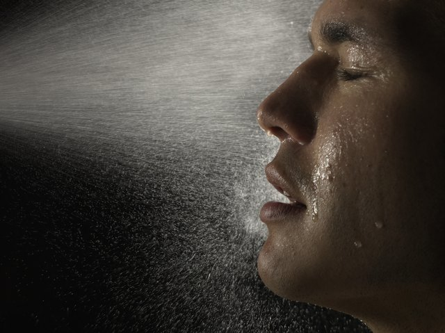 Young man being sprayed in face with water, eyes closed, side view