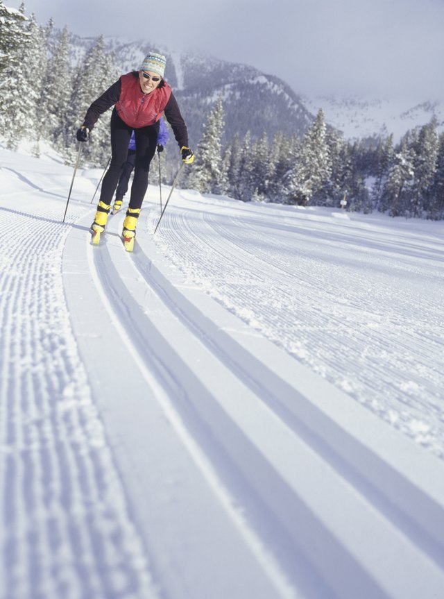 Two people skiing down track in snow