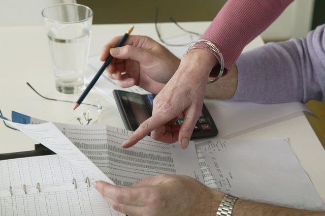Mature woman pointing to bill held by mature man at desk, close-up
