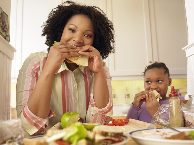 Mother and Her Young Daughter Stand in the Kitchen Eating Cheese Sandwiches for Lunch