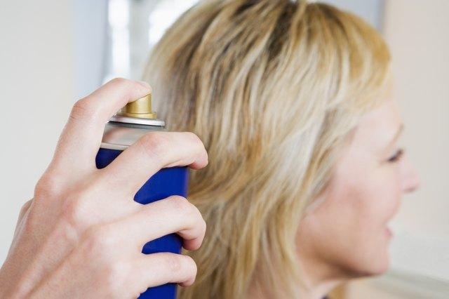 Hand spraying woman's hair