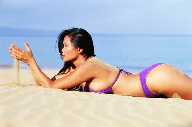 Woman in bikini lying on beach