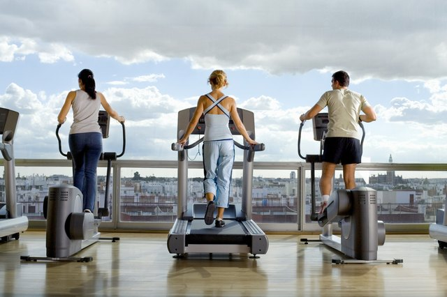 Rear view of People using exercise equipment in front of a window