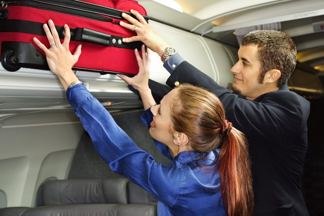 Couple putting suitcase in overhead compartment