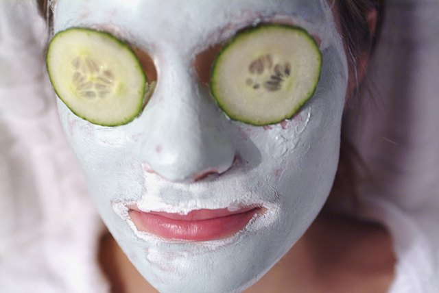 Close-up of a mid adult woman wearing a facial mask with cucumber slices on her eyes