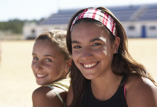Portrait of two girls (12-14) smiling, outdoors