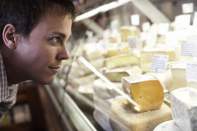 Man Looking at Cheeses