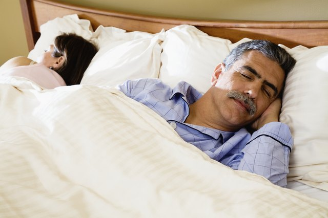 Middle-aged couple sleeping in bed