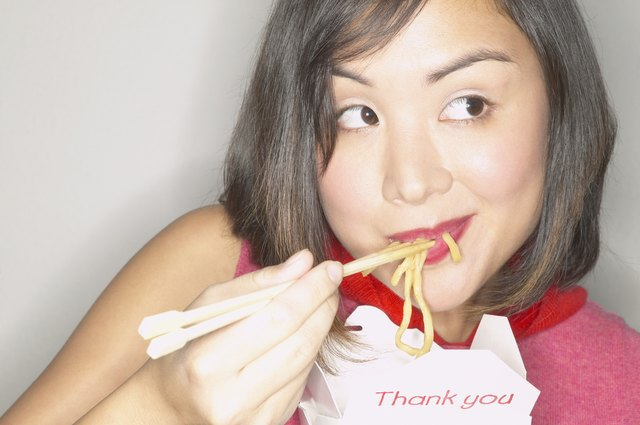 Young woman smiling eating noodles