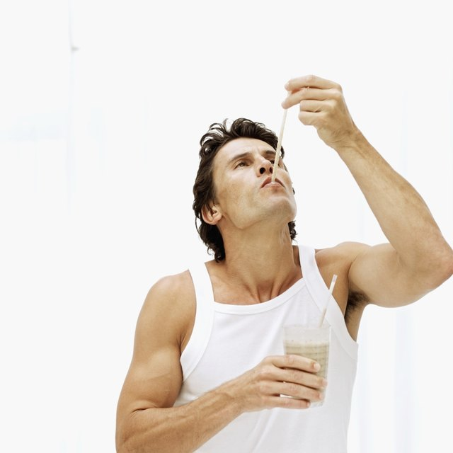 Young man sucking a straw and holding a glass of milkshake