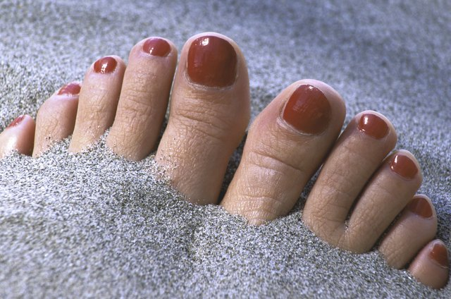 Close-up of person's toes sticking out of the sand
