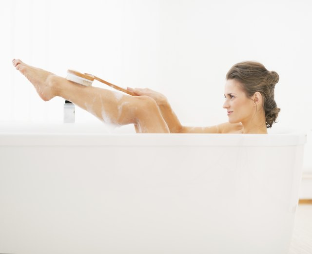 young woman in bathtub using body brush on leg