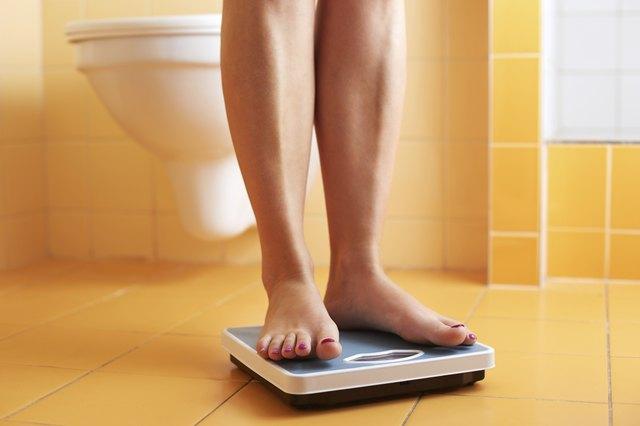 Pair of female feet on a bathroom scale