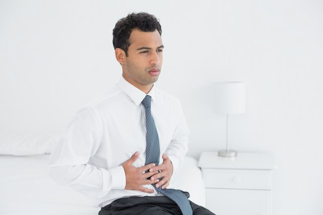 Businessman with stomach pain sitting on bed