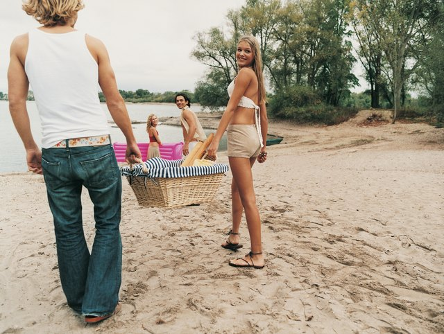 Group of Young People Arrivng at a Beach at the Edge of a Lake Carrying a Picnic Hamper and a Lilo