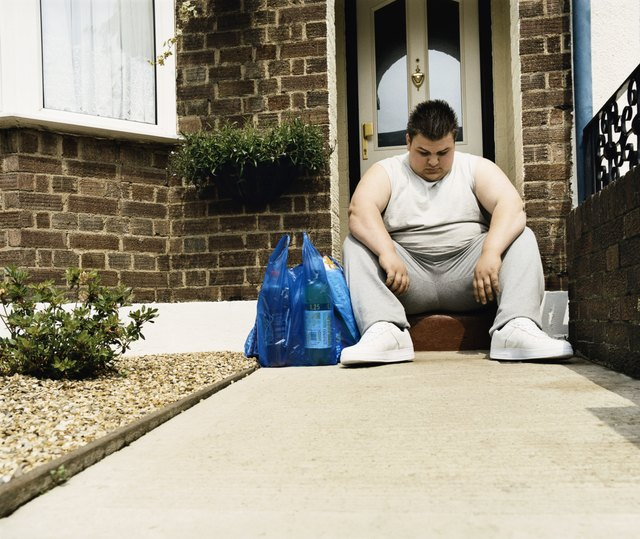 Overweight Man Sits Next to His Shopping on a Doorstep