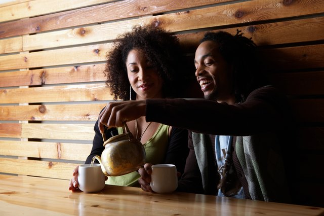 Man and woman drinking tea at table in cafe, smiling