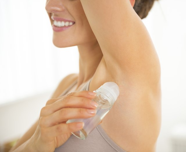 Closeup on happy young woman applying deodorant