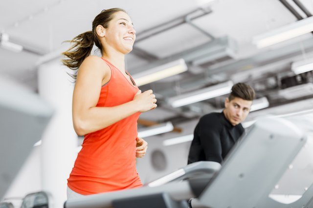 Beautiful young woman running on a treadmill in gym