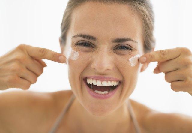 Happy woman having fun time while applying cream in bathroom