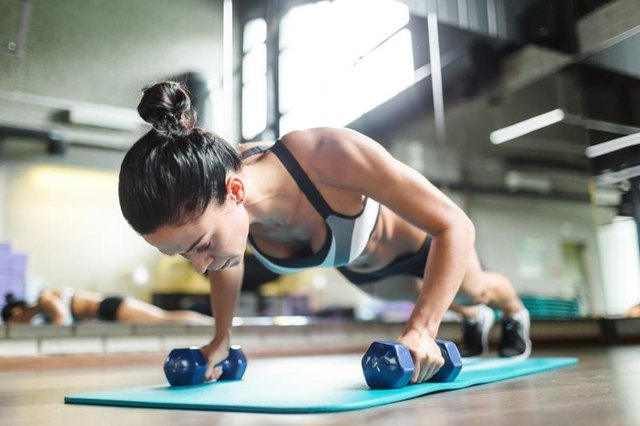 Muscular female doing planks with dumbbells