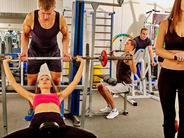 Woman working his arms and chest at gym. She lifting barbell. Man backs girl while taking exercises. Large group people background.
