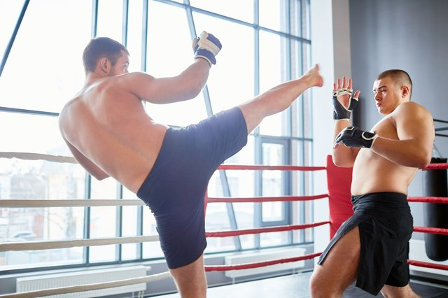 Portrait of shirtless wrestler fighting with opponent in boxing ring at fight practice: evading high kick in head