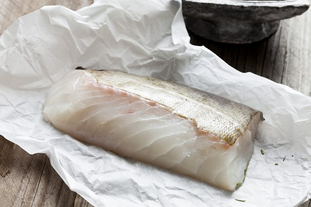 Raw fish fillet, cod on greaseproof paper