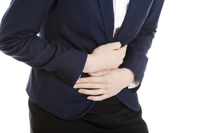 Beautiful business woman is touching her stomach.
