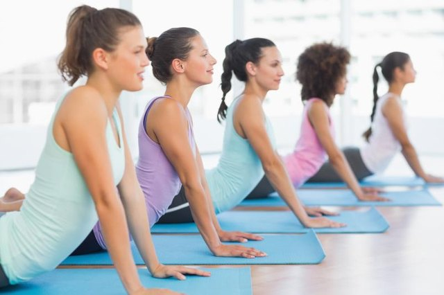 Side view of a fit class doing the cobra pose in a bright fitness studio
