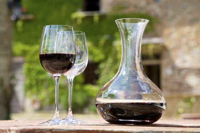 Red wine in a wine carafe and a two wine glasses in old vineyard