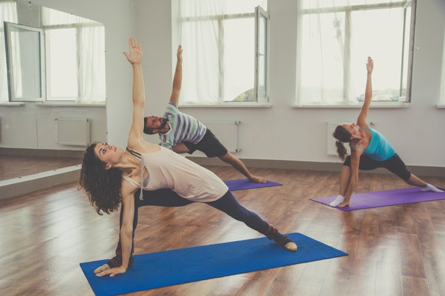 Group of people are doing yoga indoors