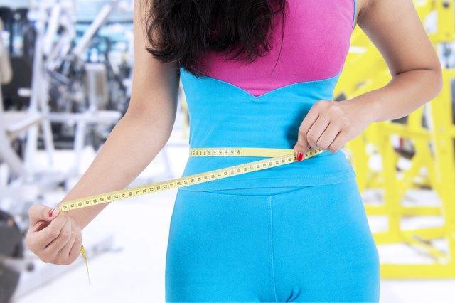 Closeup of female trainer measure her tummy