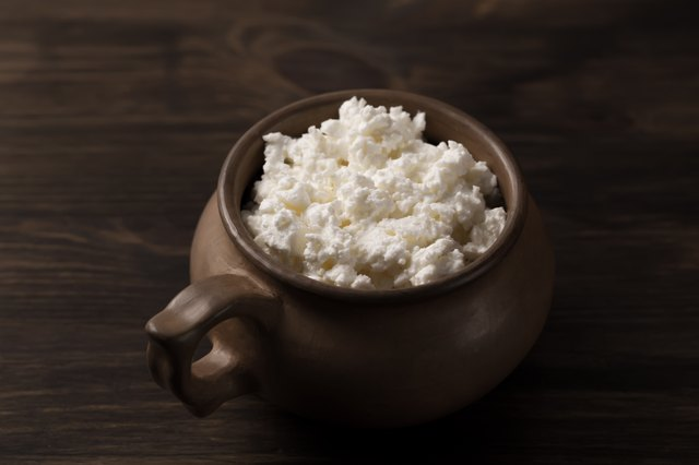 fresh tasty curd in pot on wooden background.
