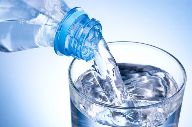 Pouring glass of water from plastic bottle on blue background