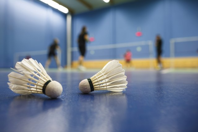 badminton courts with players competing; shuttlecocks in the foreground