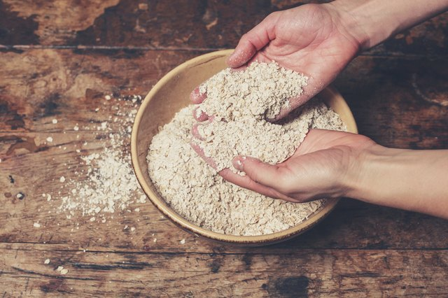 Hands mixing oats on table