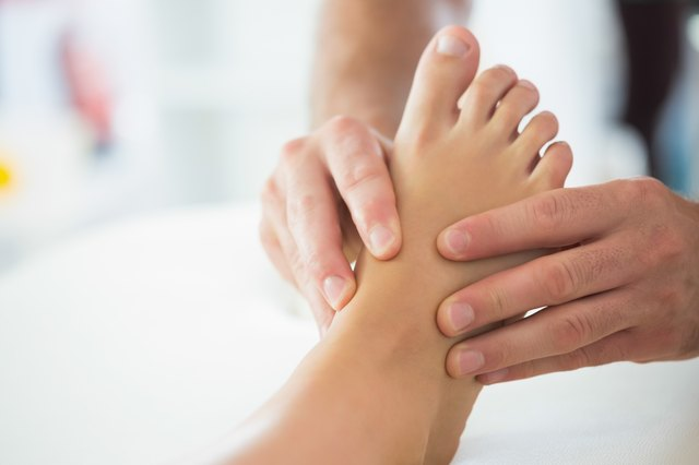 Close up of physiotherapist massaging patients foot