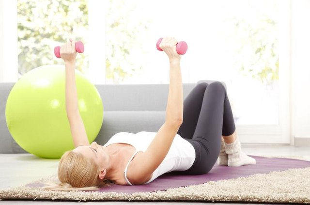 Portrait of middle age woman working out with dumbbells at home.