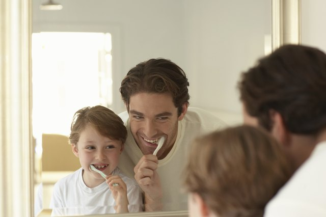 Father and son (5-7) brushing teeth, looking at reflections in mirror