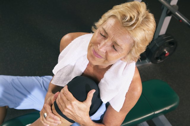 Mature woman in gym holding knee, eyes closed, overhead view
