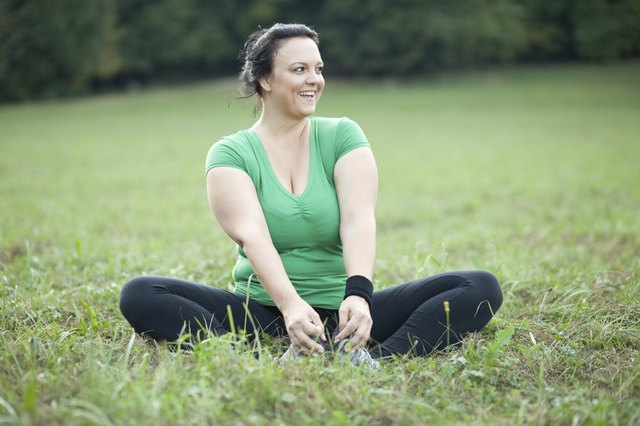 Cheerful plus sized woman stretching in the park