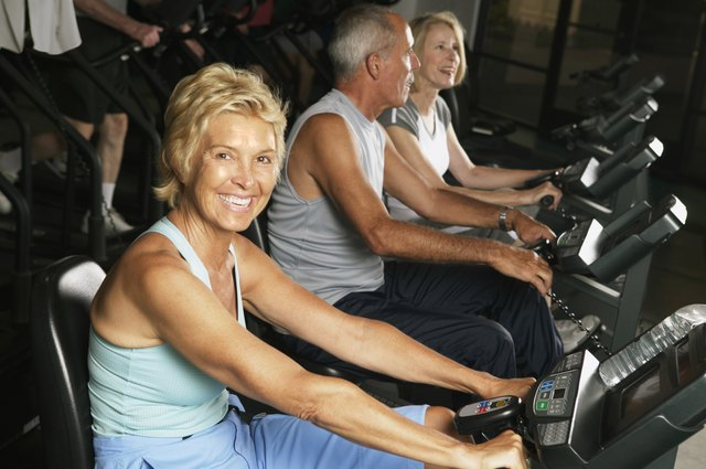 Mature woman on cycling machine in gym, smiling, portrait
