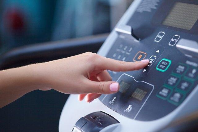 girl on a treadmill presses the button