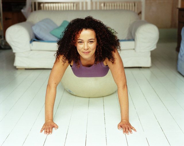 Woman doing push-ups on fitness ball in living room, smiling, portrait