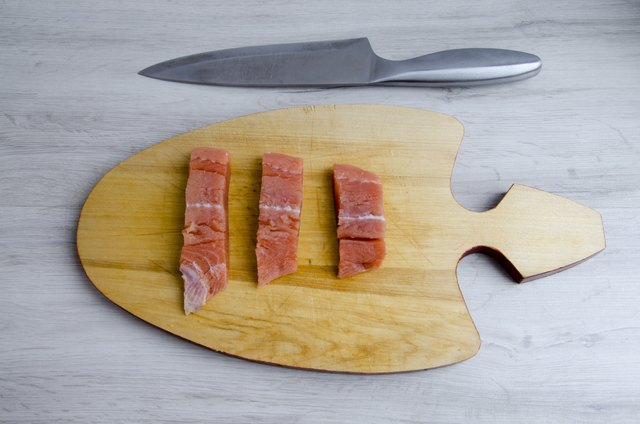 The pieces of salmon on a cutting Board and knife