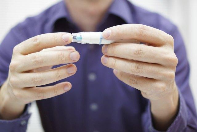 Closeup of young man using checking level of blood sugar