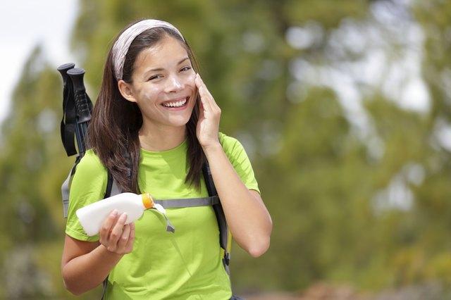 woman hiking putting sunscreen