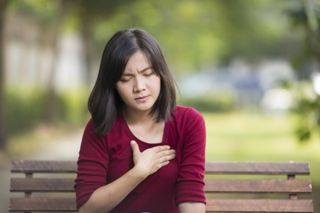 Woman Has Chest Pain Sitting on Bench at Park